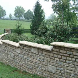 Adding the final touch to your stone retaining wall by using stone caps